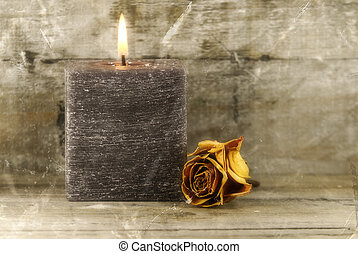 nostalgia - candle and faded rose on wooden background,...