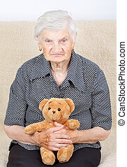 Nostalgia - Senior woman sitting with brown teddy bear