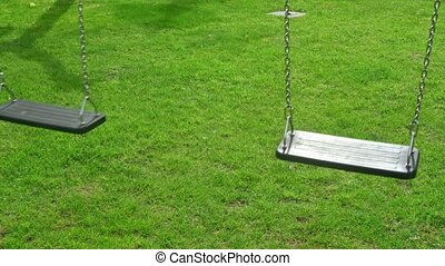 Nostalgic children swing on an empty grassy field. A symbol of loneliness and remembrance