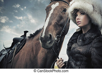 Nostalgic young brunette posing next to a horse
