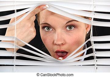 Nosy blond woman peering through blinds