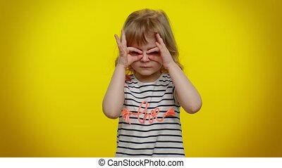 Nosy curious child girl closing eyes with hand and spying through fingers, hiding and peeping, binocular gesture, exploring way, seeking something in distance. Teen kid children on yellow background