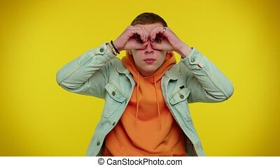 Nosy curious teen stylish boy closing eyes with hand and spying through fingers, hiding and peeping, binocular gesture, exploring way, seeking something in distance. Young man on yellow background