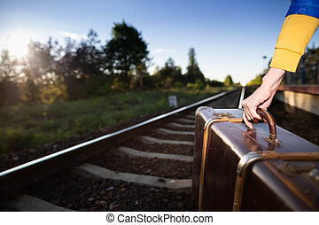 Not a safe walk on the tracks with an old travel suitcase at sunset on hot summer days.