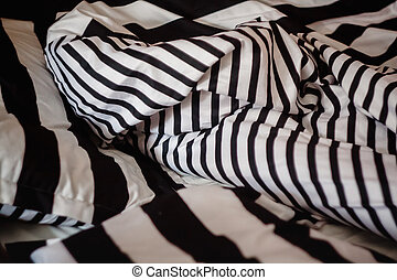 not the laid bed with a pattern of black-and-white strip, close-up.