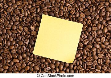 nota amarilla, papel, en, granos de café, plano de fondo