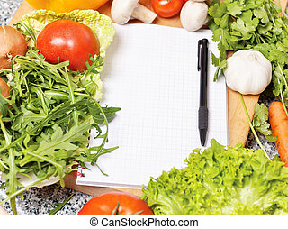 Note book among the vegetables for writing recipe
