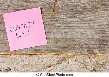Red sticky note on a wooden wall with the words Contact Us on it