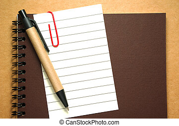 Note paper clip on notebook with pen