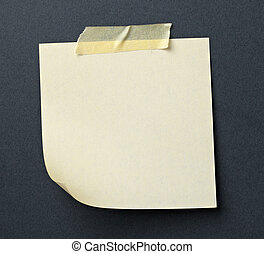 close up of note paper with adhesive tape on a gray background