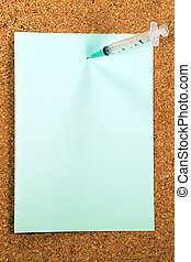 A green paper note held by a syringe on a cork medical bulletin board