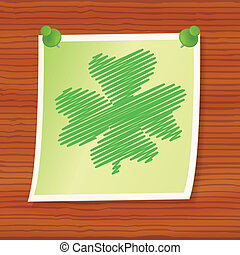 note with four-leaf shamrock pinned to wooden board