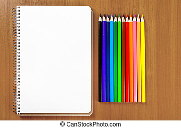 notebook and a set of colored pencils