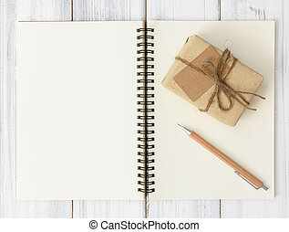 Notebook and brown pencil on wood table background