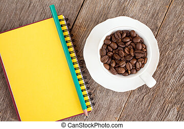 Notebook and cup with roasted coffee beans