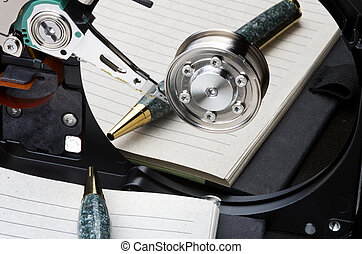 Notebook and pen mirrored in hard disk platter