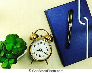 notebook and pen with alarm clock top view