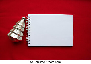 Notebook and silver Christmas tree on a red background. The concept of a New year
