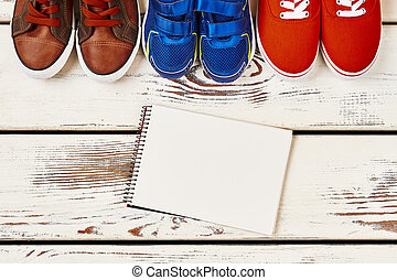 Notebook and sneakers on wood.