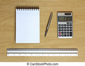 notebook calculator ruler and pen on desk