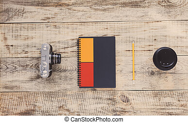 Notebook, camera, coffee cup, pencil on old wooden boards. View from above. Hipster style. Top view with copy space. Free space for text.