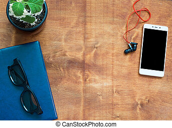 Notebook, cellphone, headphones and black glasses on wooden desk. Black blank space on the phone screen