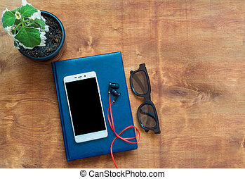 Notebook, cellphone, headphones and black glasses on wooden desk. Black blank space on the phone screen.
