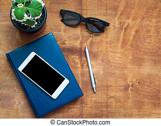 Notebook, cellphone, pen, black glasses and green flower on wooden desk. Black blank space on the phone screen