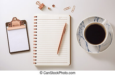 Notebook, clipboard, coffee cup and pen on desk