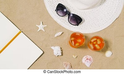 notebook, cocktails, hat and shades on beach sand -...