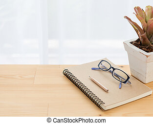 Notebook ,eyeglasses, flowerpot and brown pencil on wood table background
