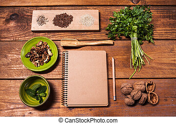 Notebook for recipes, walnuts, parsley and seeds on wooden table.