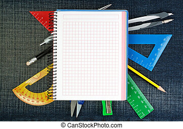 Notebook for school supplies on the background jeans.
