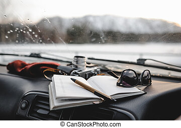 Notebook, glasses and film camera on the dashboard