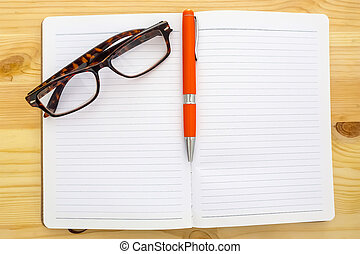 Notebook, glasses and pen on wooden background.