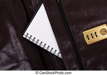 Notebook in an open brown leather briefcase