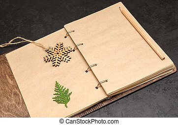 Notebook in wooden cover with kraft blank sheets, pencil, fir tree branch and wooden snowflake on black background. Plan next year concept. To do list. Christmas background. Copy space. Mockup