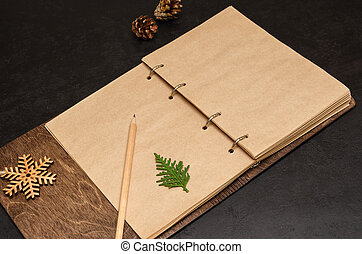 Notebook in wooden cover with kraft blank sheets, pencil, fir tree branch and wooden snowflake on black background. Plan next year concept. To do list. Christmas background. Mockup. Copy space