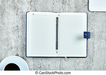 Notebook, laptop and a cup of tea on wooden desk
