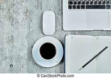 Notebook, laptop, mouse an a cup of tea on wooden desk