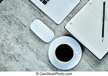 Notebook, laptop, mouse and a cup of tea on wooden desk