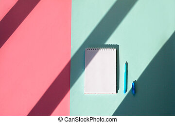 Notebook, pen and cap on a blue background, pink background copy space. Top view, with shadow.