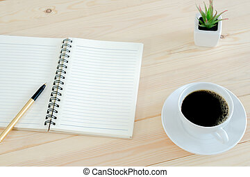 Notebook pen and cup of coffee on wood table