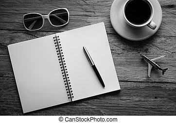 Notebook pen and cup of coffee on wood - tone black and white