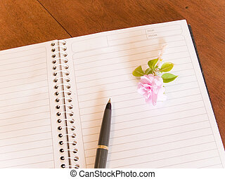 notebook, pen, and flower