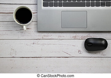 Notebook wireless mouse and a cup of coffee on the white table with copy space.