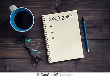 Notebook with 2019 goals massage, pencil, glasses and cup of coffee on wood background.