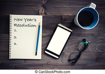Notebook with 2019 New year?s resolution massage with pencil, glasses, phone and cup of coffee on wood background.