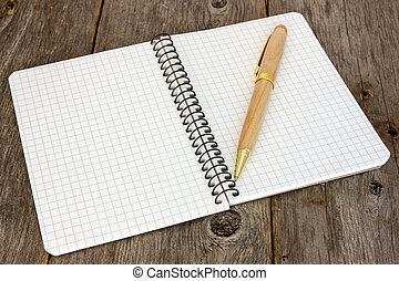 Notebook with a pen on the floor