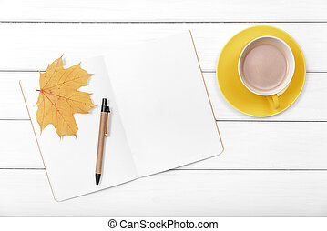Notebook with autumn leaves and coffee.